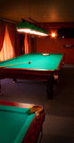 Interior of a club having billiard tables. Illuminated with lights Stock Photography
