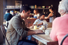 Interior Of Coffee Shop With Customers Using Digital Devices Royalty Free Stock Photos
