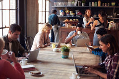 Interior Of Coffee Shop With Customers Using Digital Devices Stock Photos