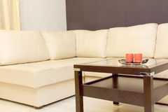 Interior with coffee table and white corner leather sofa . Stock Images