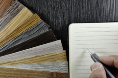 Interior color design selection concept. Top view of architects hands writting of materials sample on creative desk Royalty Free Stock Photos