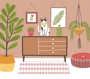 Interior of comfy room with table and cat sitting on it, potted plants, wall pictures, home decorations. Cozy house. Decorated in modern Scandinavian hygge Royalty Free Stock Images