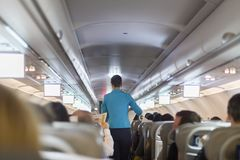 Interior of commercial airplane with stewardess serving passengers on seats during flight. Royalty Free Stock Photo