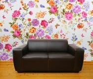 Interior con el sofá de cuero marrón contra la pared floral Imagenes de archivo