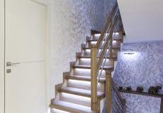 Interior con las escaleras del roble con el contraluz de la iluminación del LED imagenes de archivo
