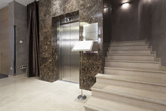 Interior of a corridor with passenger lift and marble stairs Stock Photography