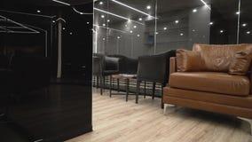 Interior costoso moderno con el sofá y el vidrio negro acci?n Espacio estrecho con las butacas y el sofá de cuero en fondo almacen de metraje de vídeo