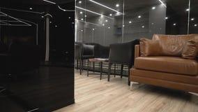 Interior costoso moderno con el sofá y el vidrio negro acci?n Espacio estrecho con las butacas y el sofá de cuero en fondo metrajes