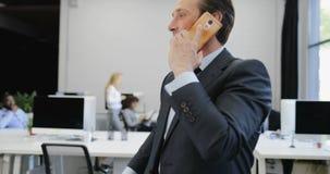 Interior coworking moderno de la oficina: hombre de negocios que hace la conversación de la llamada de teléfono de la charla sobr almacen de metraje de vídeo