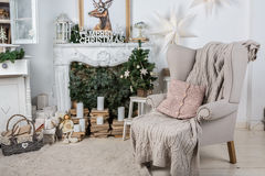 Interior with cozy big armchair. Interior room decorated in Christmas style. No people. An empty chair. Neutral colors. Home comfort of modern home. A series of Royalty Free Stock Images