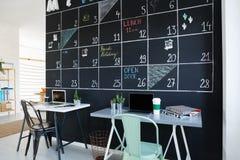 Interior with creative blackboard calendar. Office interior with creative blackboard calendar, desks and chairs Stock Photos