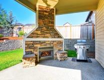 interior cubierto acogedor del patio con la chimenea y la barbacoa de piedra del ajuste foto