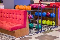 Interior da área de assento no clube do boliches Sofá e prateleiras macios vermelhos confortáveis com as bolas de boliches colori fotos de stock royalty free