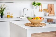 Interior da cozinha branca moderna com indução cozinhando o calefator vegetais na tabela Fotografia de Stock