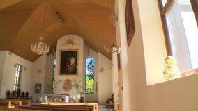 Interior da igreja nova moderna Bancos do altar e estátua do anjo no peitoril da janela filme