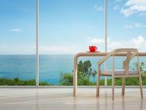 Interior da opinião do mar do escritório domiciliário com o copo de café vermelho Foto de Stock Royalty Free