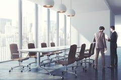 Interior da sala de conferências com cadeiras marrons, homens Imagens de Stock