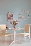 Interior da sala de jantar com a parede azul das placas decorativas das flores Imagem de Stock