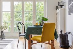 Interior da sala de jantar do vintage com uma tabela, uma cadeira amarela e uma janela grande do balcão foto de stock royalty free
