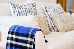 Interior da sala de visitas com do sof? branco da cor do material da tela fim bege azul dos coxins e da manta dos elementos acima fotos de stock