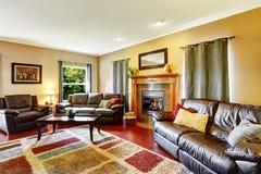 Interior da sala de visitas com sofás e a chaminé de couro Imagem de Stock