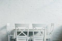 Interior da sala do jantar com tabela de madeira e das cadeiras na frente de Fotos de Stock