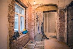 Interior da sala pequena com janela e paredes de tijolos em um apartamento que esteja sob a construção, remodelando, renovatio imagens de stock royalty free