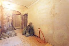 Interior da sala pequena com paredes de tijolos, dos sacos com lixo, de tubulação ondulada e do assoalho de madeira no apartament imagem de stock