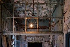Interior de construção abandonado velho da lascar-pintura com um bulbo sobre dentro Fotos de Stock Royalty Free