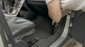 Interior de couro do carro dos hoovers do homem com o tubo plástico cinzento longo