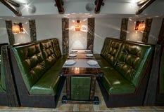 Interior de couro verde dos sofás do bar dois, tabela de madeira servida Imagens de Stock