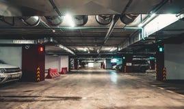 Interior de estacionamento iluminado do carro subterrâneo sob a alameda moderna com lotes dos veículos foto de stock