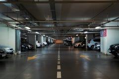 Interior de estacionamento iluminado do carro subterrâneo sob a alameda moderna com lotes dos veículos e das setas no assoalho imagens de stock