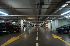 Interior de estacionamento iluminado do carro subterrâneo sob a alameda moderna com lotes dos veículos e das setas no assoalho imagem de stock