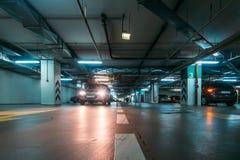 Interior de estacionamento iluminado do carro subterrâneo sob a alameda moderna com lotes dos veículos e das setas no assoalho imagem de stock royalty free