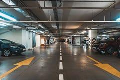 Interior de estacionamento iluminado do carro subterrâneo sob a alameda moderna com lotes dos veículos e das setas no assoalho foto de stock royalty free