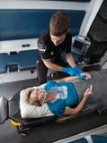 Interior de la ambulancia con el paciente mayor Imagen de archivo libre de regalías