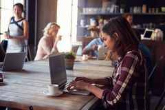 Interior de la cafetería con los clientes que usan los dispositivos de Digitaces fotos de archivo