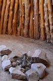 Interior de la choza con el hoyo del fuego de las rocas Imagenes de archivo