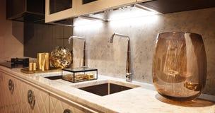 Interior de la cocina con dos grifos en tonos marrones calientes con los accesorios de cristal foto de archivo