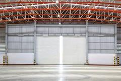 Interior de la fábrica con la puerta del obturador Fotos de archivo