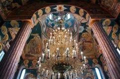 Interior de la iglesia ortodoxa con la lámpara masiva y las pinturas coloridas Imagen de archivo