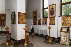 Interior de la iglesia ortodoxa y mujer de rogación imagenes de archivo