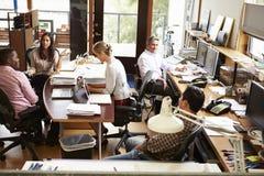 Interior de la oficina de arquitecto ocupada con el funcionamiento del personal
