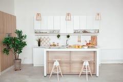 Interior de la pequeña cocina blanca con la fruta fresca, dos vidrios de zumo de naranja, baguette, caviar rojo, cruasán y Foto de archivo