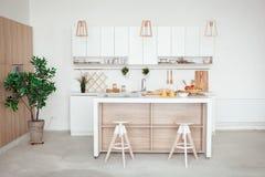Interior de la pequeña cocina blanca con la fruta fresca, dos vidrios de zumo de naranja, baguette, caviar rojo, cruasán y Fotografía de archivo libre de regalías