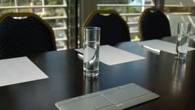 Interior de la sala de conferencias con la tabla, cruda vacíos de sillas, de papeles y de vidrios con agua metrajes