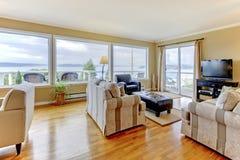 Interior de la sala de estar con la opinión del agua y las ventanas grandes Fotos de archivo libres de regalías