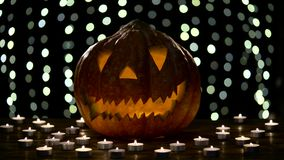 Interior de las luces de la calabaza de Halloween con la llama en un fondo negro del bokeh con las velas encendidas almacen de video