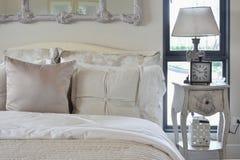 Interior de lujo del dormitorio con la lámpara de mesa y el reloj clásicos del estilo imagen de archivo